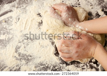 Making dough by female hands on wooden table background - stock photo