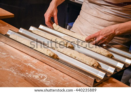 Making dough by female hands on wooden table background. preparing in bakery. baguette on a metal baking tray - stock photo