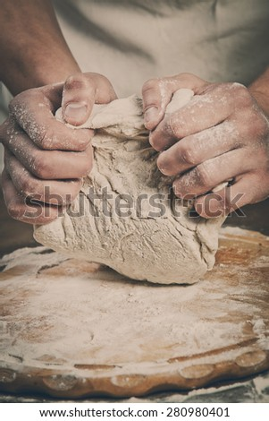 Making dough by men hands on wooden table background