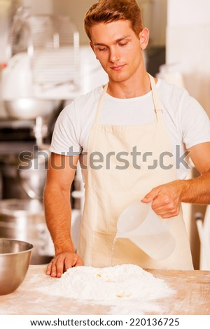 Making dough for pastry. Confident young male baker pouring water on the flour  - stock photo