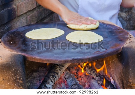 Making flour tortillas. Oven with firewood. - stock photo