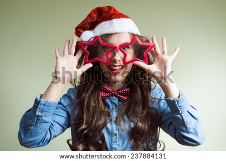 making funny eyes hipster girl in super size star shape glasses wearing xmas santa hat over olive copy space background, happy smiling and looking at camera - stock photo