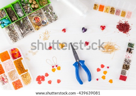 Making handmade jewelry. Boxes with beads, pliers, threads, equipment and accessories for handmade on wooden table. Process of needlework. Top view - stock photo