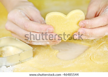 Making heart shaped shortbread cookies with cutters - stock photo
