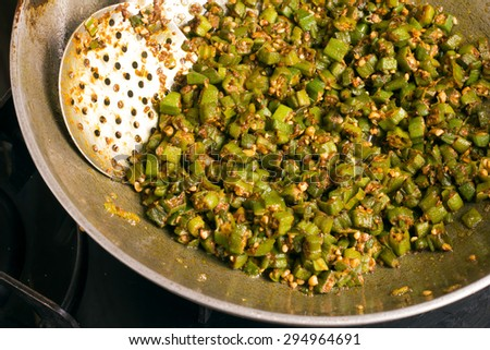 making home made masala bhindi or ladyfinger in karahi using spatula - stock photo