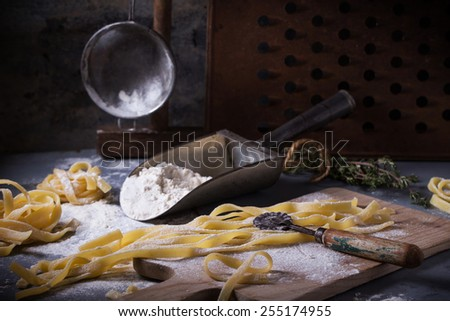 Making homemade pasta linguine on rustic kitchen table with flour, vintage sieve and cutting board. See series. - stock photo