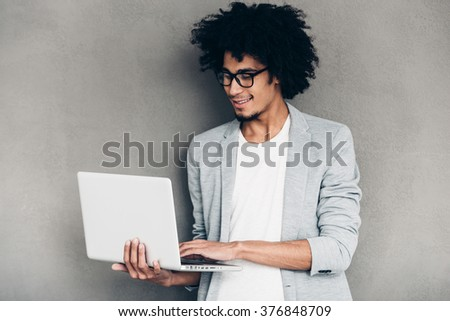 Making ideas happen. Cheerful young African man using laptop and smiling while standing against grey background - stock photo