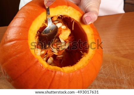Making Jack o lantern. Scooping out the pumpkin.