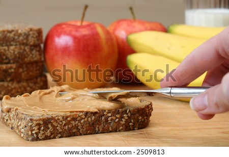 Making lunch, peanut butter sandwich. Apples, bananas and a glass of milk in the background. - stock photo