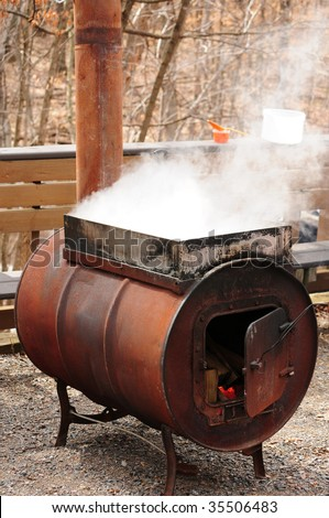 Making maple syrup - steam rising off a vat of sap being boiled on an outdoor stove - stock photo