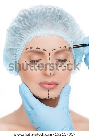 Making marks on face. Close-up of beautiful young woman in medical headwear keeping eyes closed while doctors hands in gloves making marks on her face isolated on white - stock photo