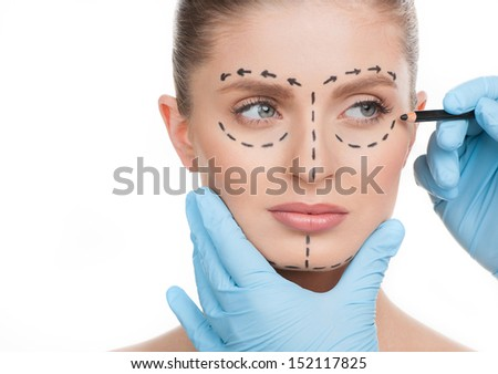 Making marks on face. Portrait of beautiful young woman looking away while doctors hands in gloves making marks on her face isolated on white - stock photo
