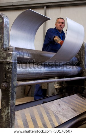 Making metal pipes and tubes in an engineering factory - stock photo