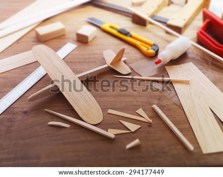 Making model airplane from wood. Wooden air plane handcrafted with balsa wood, on work table by the window. Airplane, cutter knife, balsa wood material and glue on table. - stock photo