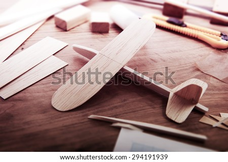 Making model airplane from wood. Wooden air plane handcrafted with balsa wood, on work table. tools and Materials on table. Intentionally shot in retro-impression color, and shallow depth of field. - stock photo