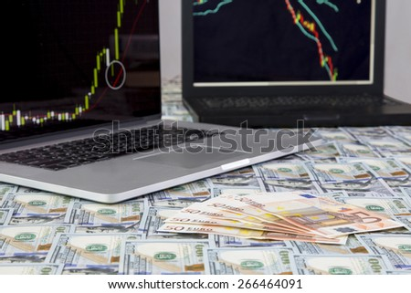 Making money. Desk covered with flat layer of US and European cash notes and two laptops on the background with Forex charts: bullish and bearish - stock photo