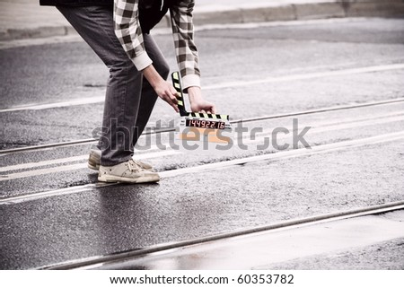 Making movie and slate holding by a man on wet road - stock photo