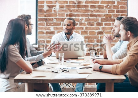 Making new strategy. Group of young people discussing something while sitting at the wooden table in the office - stock photo