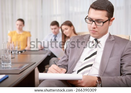 Making notes. Selective focus on young businessman in suit and tie putting down his remarks to the note book while his team sitting around the table in blurry