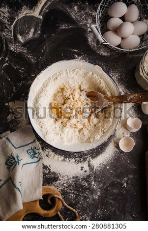 Making of dough for egg pasta, or bread, or biscuit cake over blackboard from above. Rustic composition style.  - stock photo