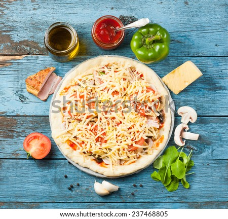 Making of pizza original set including tomatoes, mushrooms, cheese, arugula, ketchup and olive oil all placed on blue aged wooden surface, top view  - stock photo