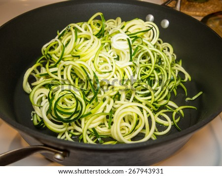 Making of spiral zucchini spaghetti imitation noodles. - stock photo