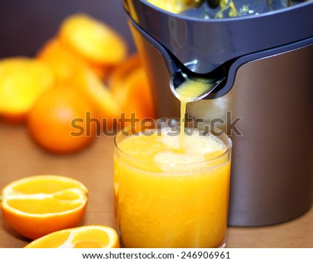 Making orange juice from sliced oranges - stock photo