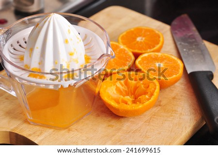 Making orange juice, Half orange with squeezer - stock photo