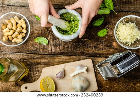 Making pesto - basil cheese, nuts, and olive oil in mortar - stock photo