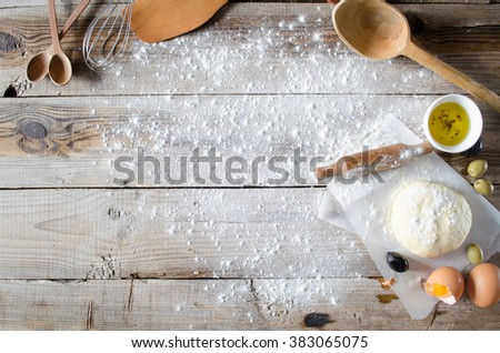 Making pie: Dough, rolling-pin and wheat flour on wooden table - stock photo