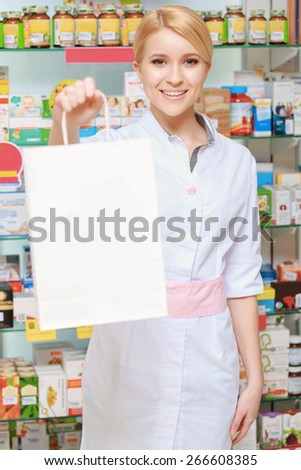 Making purchases in a pharmacy. Selective focus on a young smiling female pharmacist stretching out a blurred paper bag copyspace  - stock photo