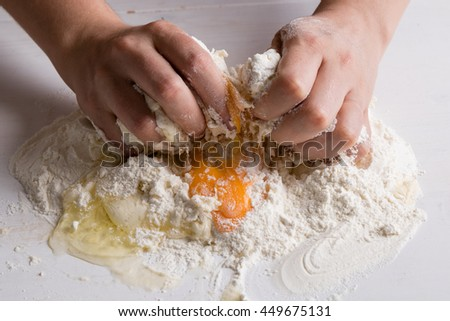 making raw dough by female hands on white table - stock photo