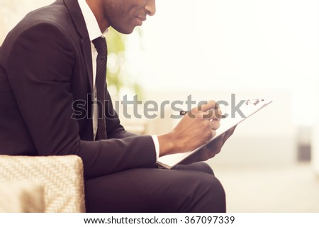 Making some business notes. Side view close-up image of cheerful young African businessman writing something in his note pad and smiling while sitting on the chair - stock photo