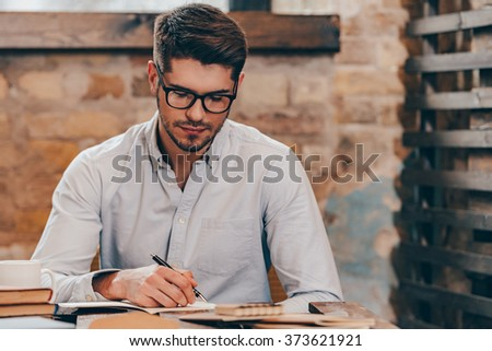 Making some notes. Handsome young man in glasses writing in his note pad while sitting at his working place - stock photo