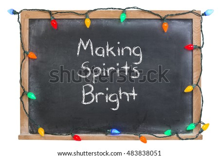 Making spirits bright written in white chalk surrounded with colored lights on a black chalkboard isolated on white