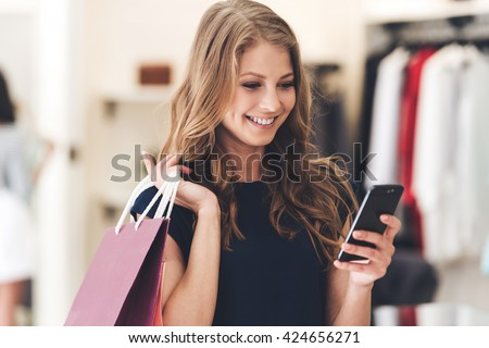 Making the retail connection. Beautiful young woman with shopping bags using her smart phone with smile while standing at the store - stock photo