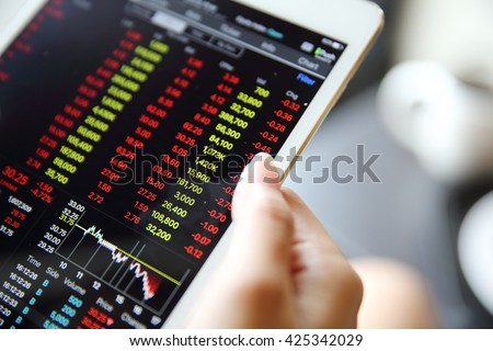 Making trading online on the tablet with bussiness woman hand - stock photo