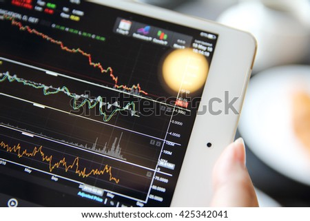 Making trading online on the tablet with bussiness woman hand