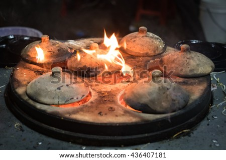 Making Vietnamese Sizzling cake (pancake), named for the loud sizzling sound it makes when the rice batter is poured into the hot skillet.
