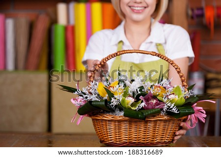 Making your life bright and colored. Cropped image of young blond hair woman in apron stretching out basket full of flowers and smiling - stock photo