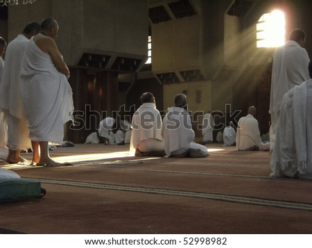 MAKKAH - DEC 11 : Muslim pilgrims in 'ihram' clothes pray at one of the mosques Dec 11, 2007 in Makkah. 'Ihram' clothes consist of two unhemmed white clothes intended to make everyone appear the same. - stock photo