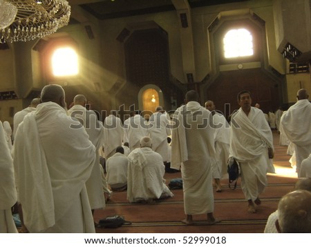 MAKKAH - DEC 27 : Muslim pilgrims in 'ihram' clothes pray at one of the mosques Dec 27, 2007 in Makkah. 'Ihram' clothes consist of two unhemmed white clothes intended to make everyone appear the same. - stock photo