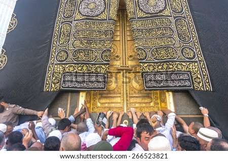MAKKAH - MAR 14 : A close up view of kaaba door and the kiswah (cloth that covers the kaaba) at Masjidil Haram on March 14, 2015 in Makkah, Saudi Arabia. The door is made of pure gold.  - stock photo