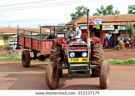 Makuyuni, Arusha, Tanzania - February 13, 2008: African, Tanzanian farmer tractor driver, sitting behind the wheel of a agrimotor without a cab, with bodywork trailer. - stock photo