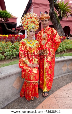MALACCA,MALAYSIA-JAN 1: Malay couple in their traditional Malacca Malay costume on JAN 1,2012 in Malacca.The Malacca Malay matrimonial gown and accessory are the mixture of Malay and Chinese influence