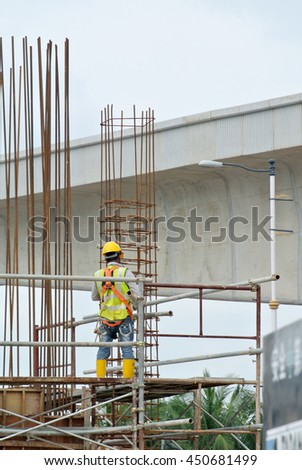 MALACCA, MALAYSIA -MAY 27, 2016: Construction workers fabricating steel reinforcement bar at the construction site in Malacca, Malaysia. The reinforcement bar was ties together using tiny wire.