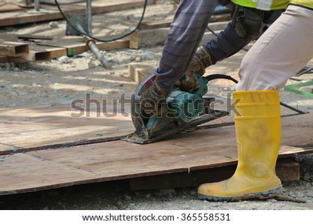 MALACCA, MALAYSIA â?? OCTOBER 05, 2015: Carpenter using electrical powered circular saw to cut timber at the construction site in Malacca, Malaysia
