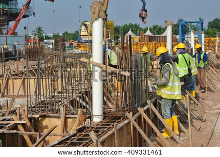 MALACCA, MALAYSIA -OCTOBER 13, 2015: Construction workers fabricating steel reinforcement bar at the construction site in Malacca, Malaysia. The reinforcement bar was ties together using tiny cable.   - stock photo