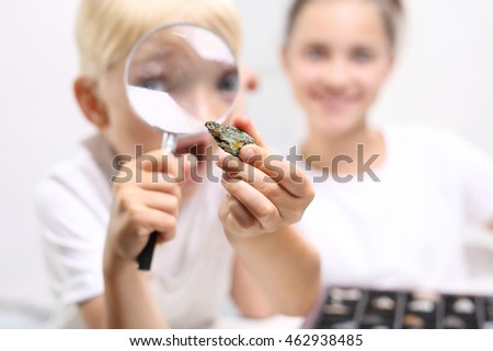 Malachite, a child watching a collection of rocks and minerals. Two children, a girl and a boy watching through a magnifying glass stones from his collection of rocks.