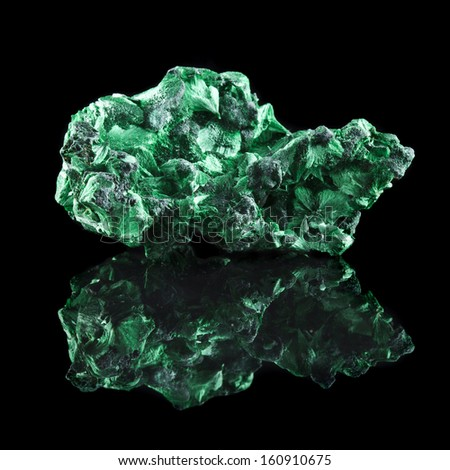 malachite mineral stone close up with reflection on black surface background - stock photo